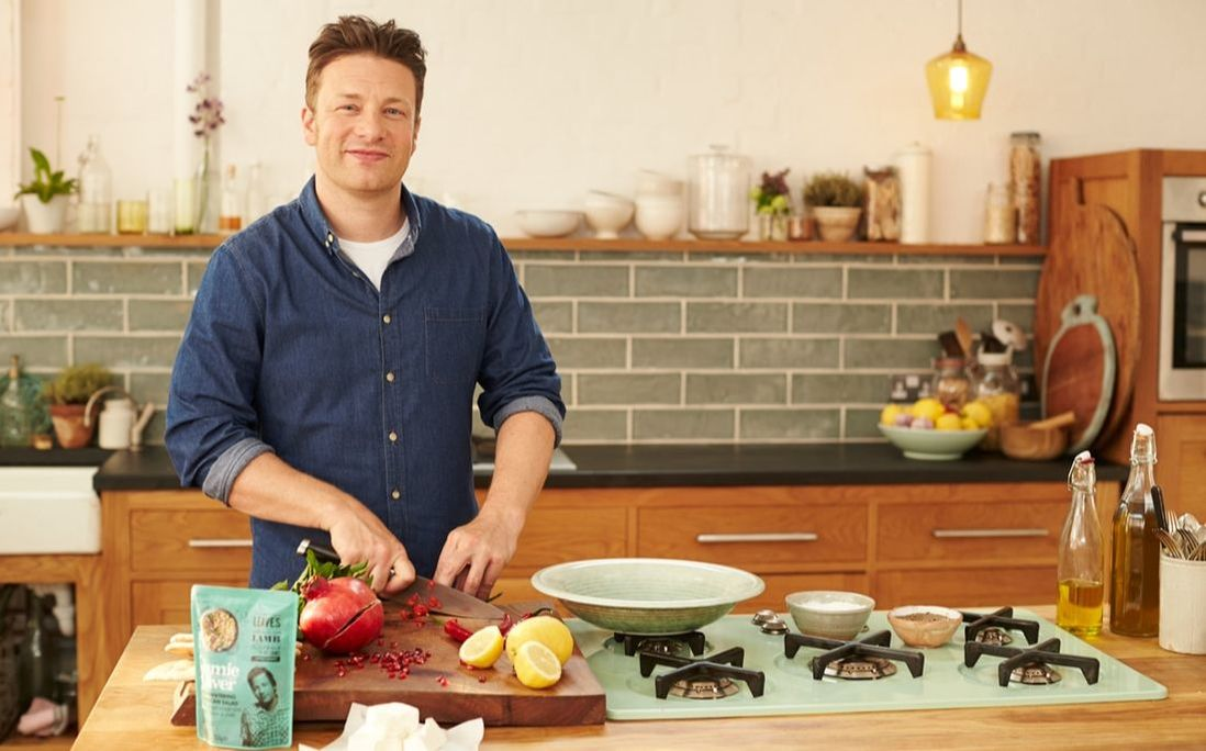 Jamie Oliver in the kitchen slicing tomatoes. grains