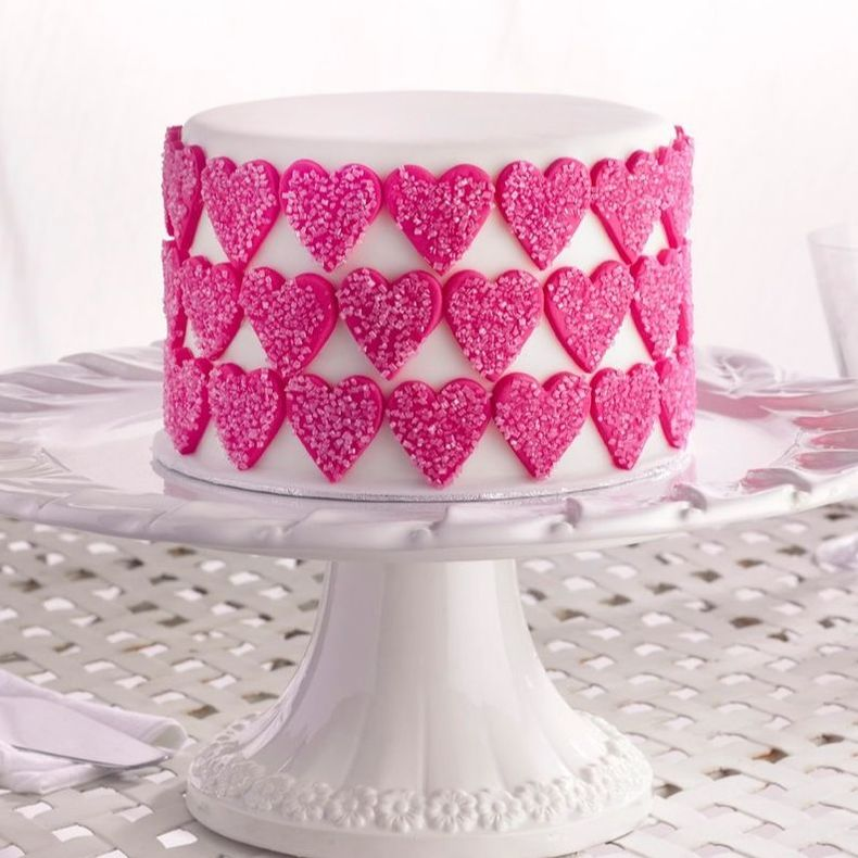 White cake with pink fondant hearts by cake angels